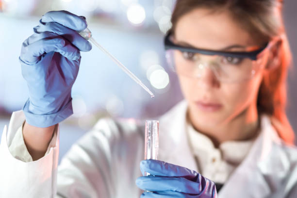 Young scientist pipetting in life science laboratory. Life scientists researching in laboratory. Focused female life science professional pipetting solution into the glass cuvette. Lens focus on pipette. Healthcare and biotechnology concept. biotechnology stock pictures, royalty-free photos & images