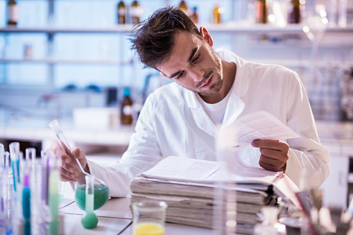 Male chemist sitting in a laboratory and doing some research while reading scientific books.