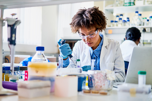 Young female scientist sitting at a table in a lab using a pipette to analyze a sample while working in a lab