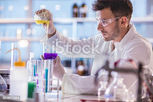 Male chemist mixing chemical substances in a laboratory.