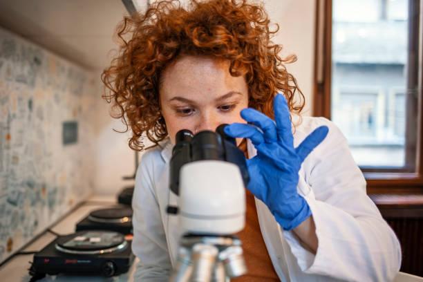 young scientist working with the microscope - ematologia foto e immagini stock