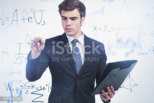 Handsome young scientist in dark suit writing formula on glassboard. Concept of science and education. Toned image double exposure