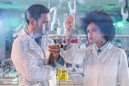 499203366 istock photo Young scientists cooperating while examining liquid in a beaker while working in laboratory. 1060404960