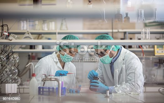 499203366 istock photo Young scientists mixing substances while working on scientific experiment in laboratory. 931640980