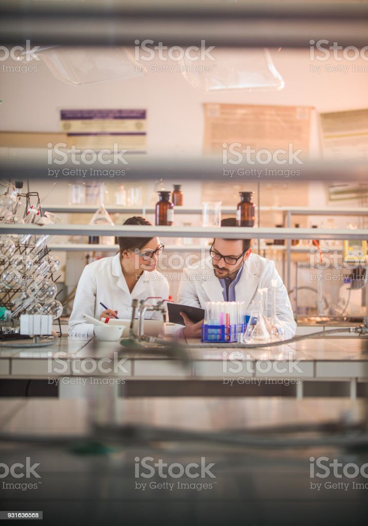 Two biochemists analyzing medical data while working on genetic...