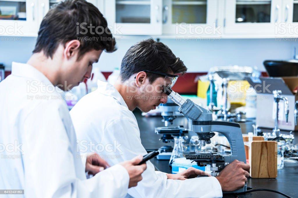 Junge wissenschaftler mit mikroskop machen test im klinischen