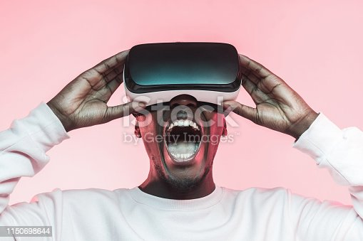 istock Young screaming african man experiencing virtual reality with VR headset, isolated on pink background 1150698644