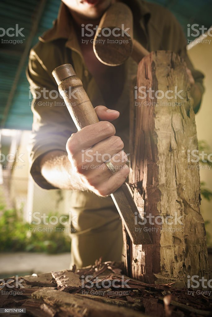 Young Sculptor Artist Working And Sculpting Wood Statue-3 stock photo