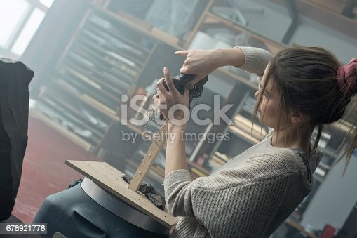517780131 istock photo Young sculptor creates a clay sculpture 678921776