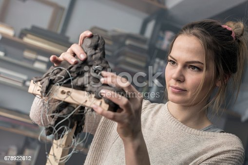 517780131 istock photo Young sculptor creates a clay sculpture 678922612