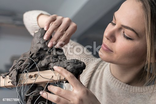 517780131 istock photo Young sculptor creates a clay sculpture 678927694