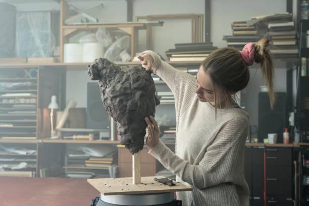joven escultor crea una escultura de arcilla - clase de arte fotografías e imágenes de stock
