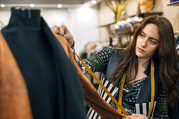 Young seamstress in a fashion store Beautiful woman measuring with a tape measure fashion designer stock pictures, royalty-free photos & images