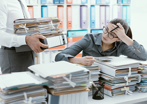 istock Young secretary overwhelmed by work 916423726