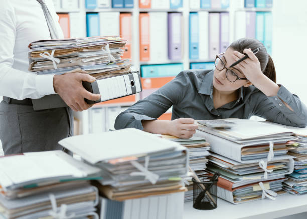 Young secretary overwhelmed by work Young stressed secretary in the office overwhelmed by work and desk full of files, her boss is bringing more paperwork to her full stock pictures, royalty-free photos & images