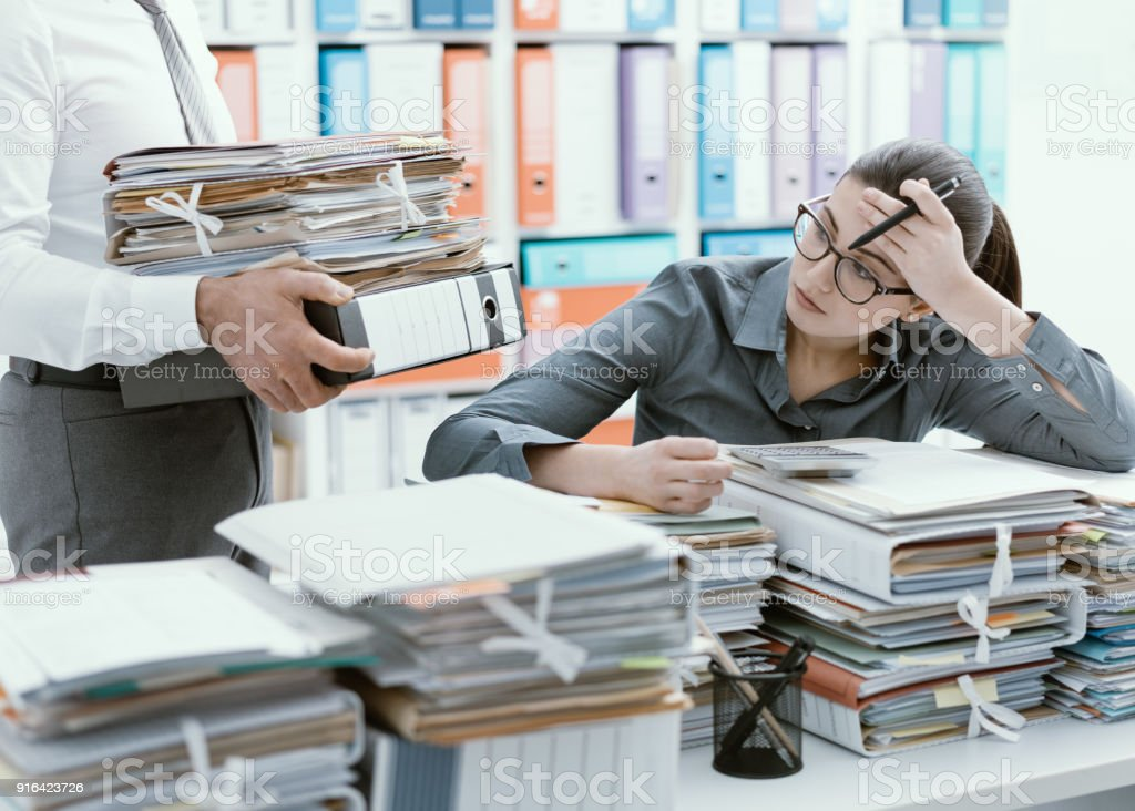 Young secretary overwhelmed by work stock photo