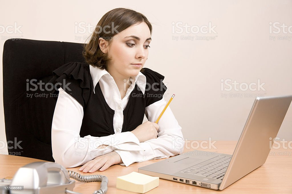 Young secretary with telephone, laptop and pencil thinking royalty-free stock photo