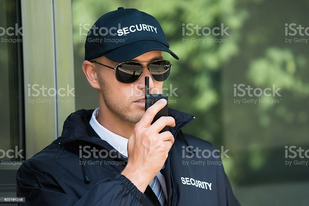 Young Security Guard Talking On Walkie-talkie stock photo