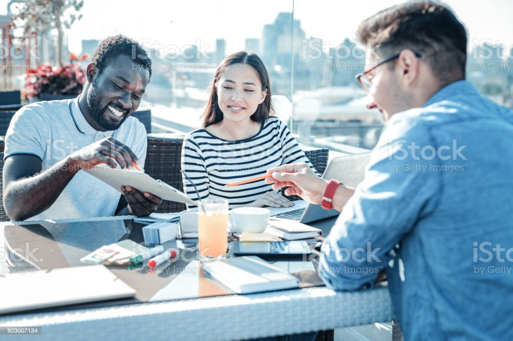 Help is what really matters. Group of millennial freelancers smiling...