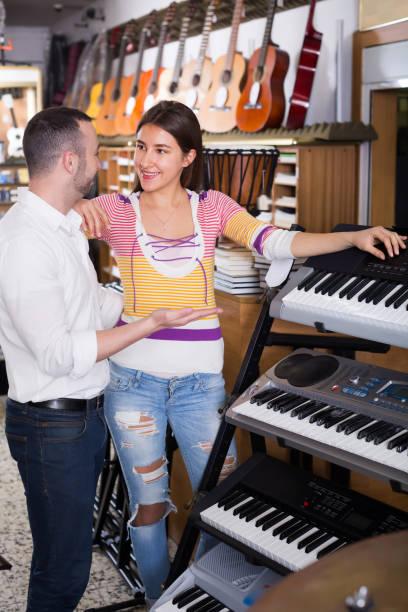 junger verkäufer helfen mann synthesizern auswählen - klavier verkaufen stock-fotos und bilder
