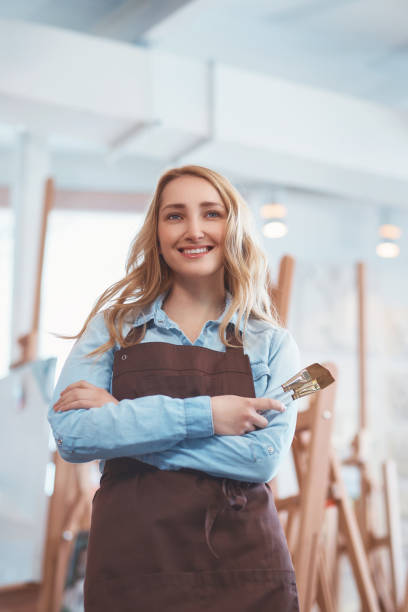 Young seller in uniform in the art store stock photo