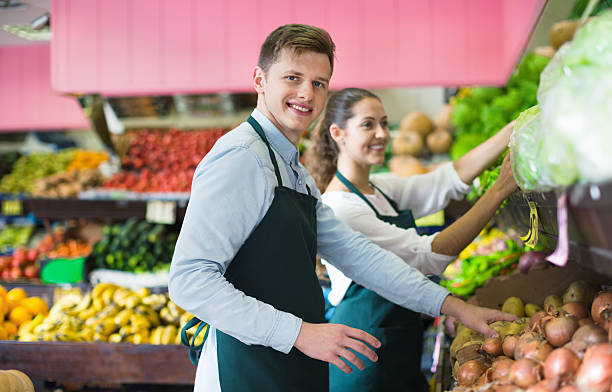 Young sellers having vegetables and fruits on displays stock photo