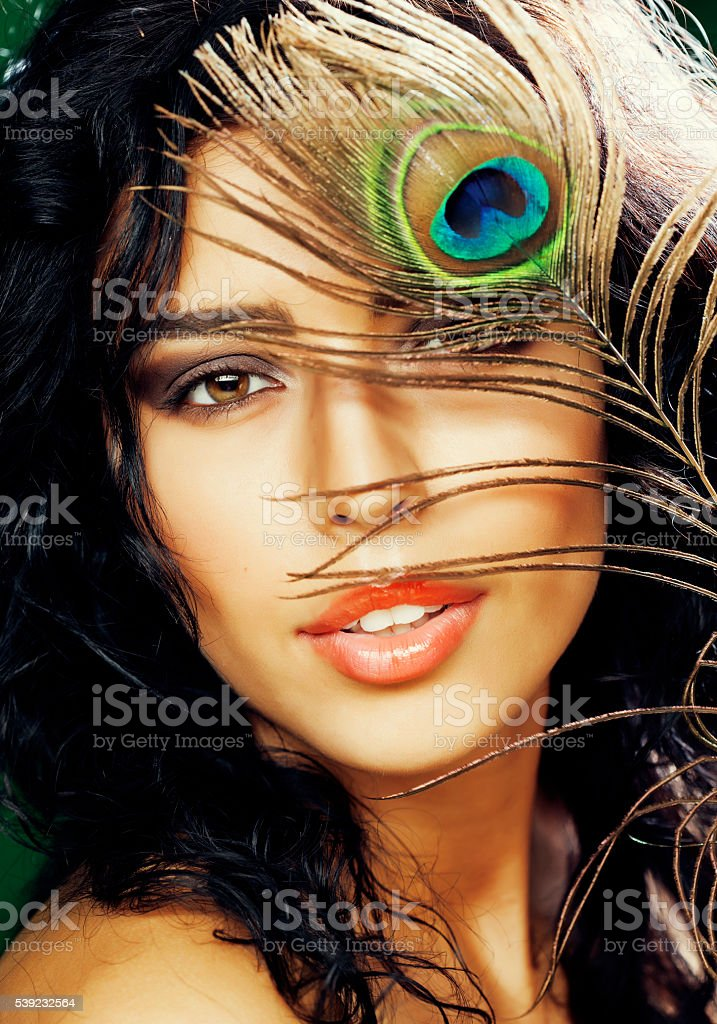 young sensitive brunette woman with peacock feather eyes close up royalty-free stock photo