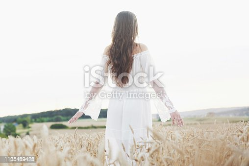 Young sensitive girl in white dress posing in a field of golden wheat.