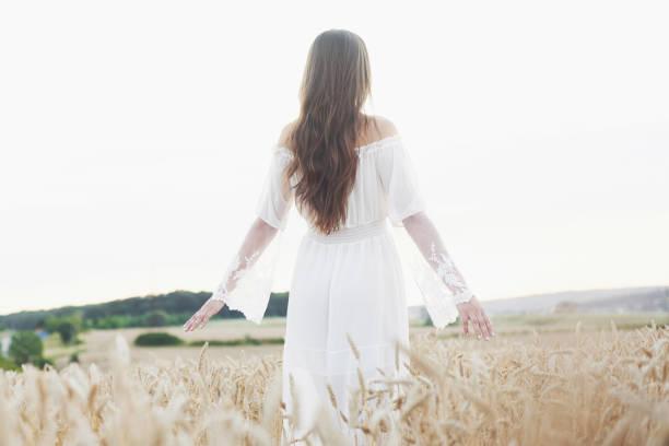 altın buğday alanında poz beyaz elbise genç hassas kız - beyaz elbise stok fotoğraflar ve resimler