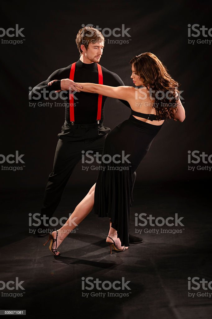 Young sensual couple dancing the tango isolated on black stock photo
