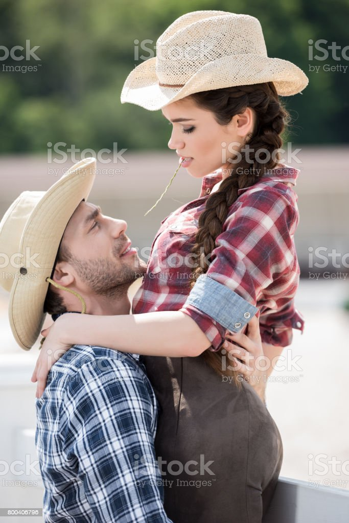 young sensual cowboy style couple hugging with straw stock photo