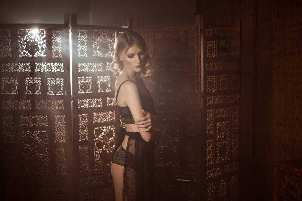 Young sensual woman in a retro lace lingerue posing against wooden carved screen stock photo