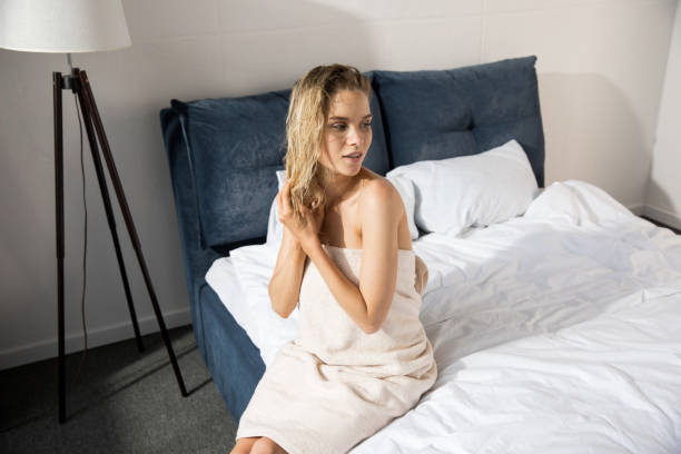 Young sensual woman wrapped up with bath towel sitting on bed and looking away Young sensual woman wrapped up with bath towel sitting on bed and looking away wet hair stock pictures, royalty-free photos & images
