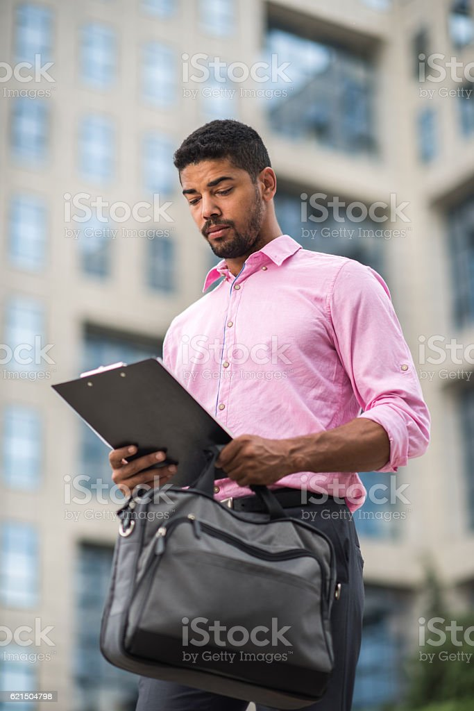 Young serious African American businessman reading data from clipboard. Lizenzfreies stock-foto
