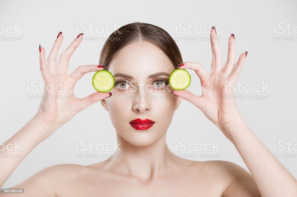 Young serious beautiful woman holding cucumber slices on the face looking at you camera isolated white grey background wall stock photo