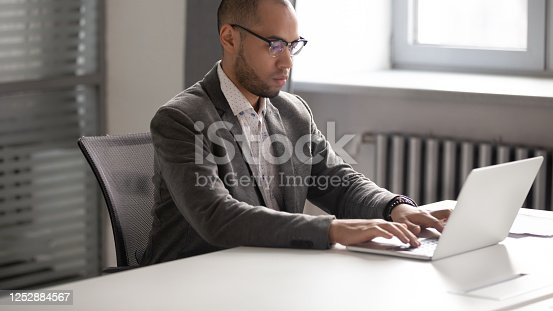 1053499704 istock photo Young serious businessman working with laptop in boardroom. 1252884567
