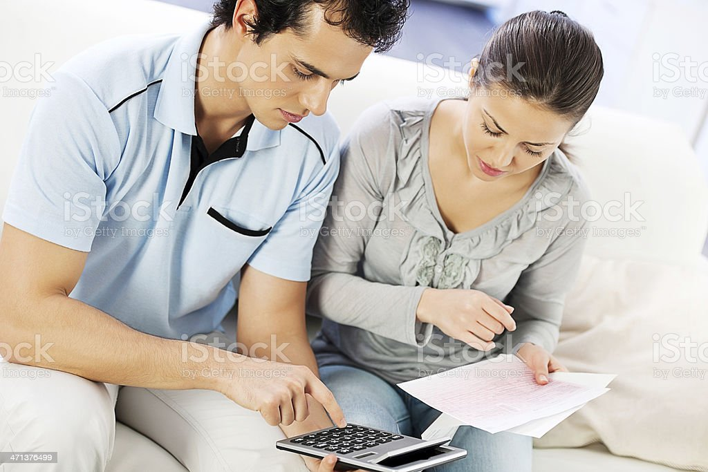 Young serious couple doing their taxes. stock photo