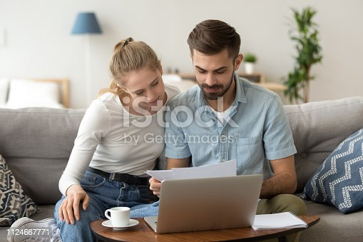 istock Young serious couple reading financial documents checking bills with laptop 1124667771