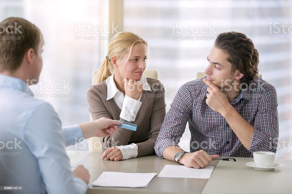 Young serious couple with agent stock photo
