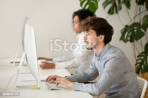 istock Young serious employee focused on computer work in multiracial office 953656120