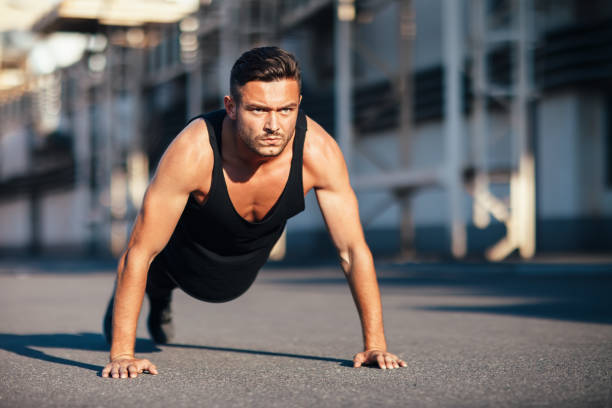 young serious man doing pushups outdoor on industrial background - man city exercise abs foto e immagini stock