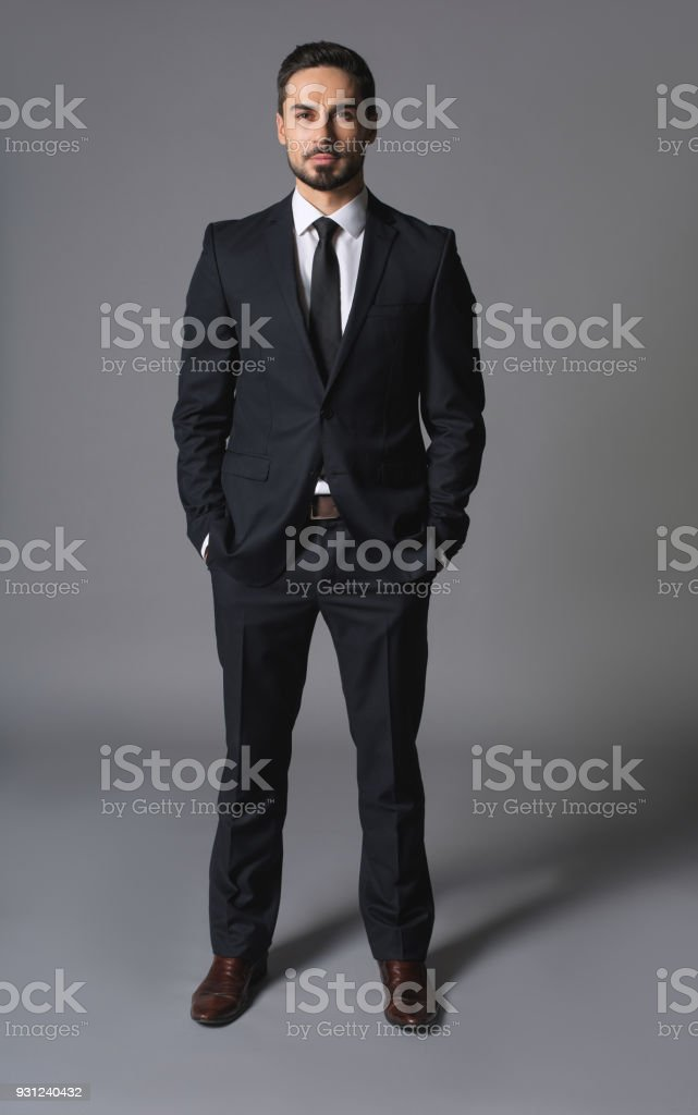 Young serious successful businessman standing with hands in pockets stock photo