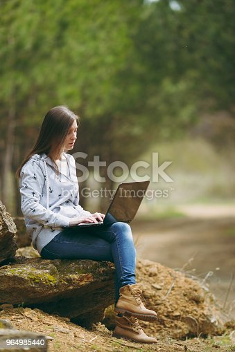 862602714 istock photo Young serious successful smart business woman or student in casual clothes sitting on stone using laptop in city park or forest working outdoors on green blurred background. Mobile Office concept. 964985440