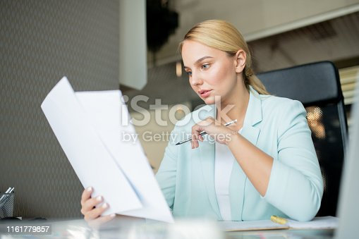 istock Young serious teacher with pencil checking papers of students 1161779857