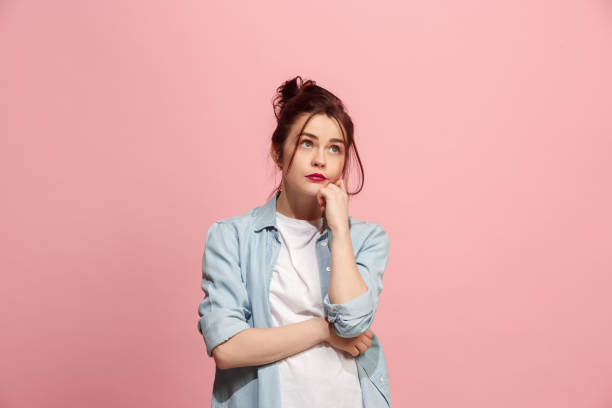 Young serious thoughtful business woman. Doubt concept stock photo