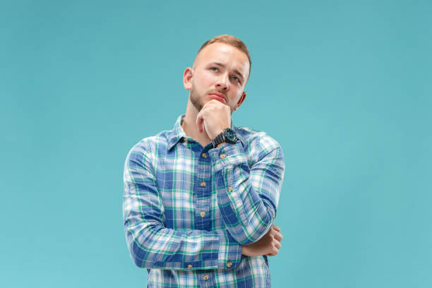 Young serious thoughtful businessman. Doubt concept. Remember all. Let me think. Doubt concept. Doubtful, thoughtful man remembering something. Human emotions, facial expression concept. Studio. Isolated on trendy blue skeptic stock pictures, royalty-free photos & images