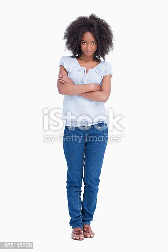 istock Young serious woman crossing her arms while standing upright 825148200