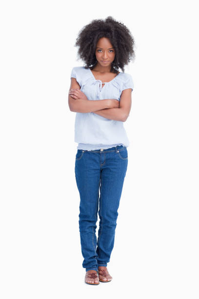 Young serious woman crossing her arms while standing upright - foto stock