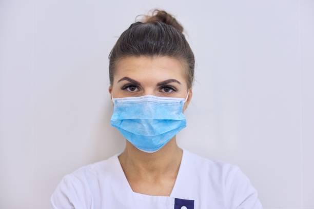 Joven mujer seria doctora con máscara médica mirando a la cámara - foto de stock
