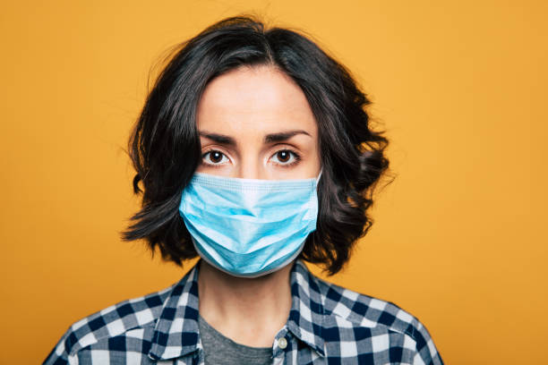 young serious woman in a protective medical mask. - mask stock pictures, royalty-free photos & images